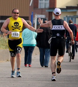 Extending the hand of friendship – The fun of triathlon is there for all to see as COLT and Pirate exchange greetings. Chris was just about to finish whilst I was just heading out on the run at the Fleetwood Sprint. We would be record PB's that day.  ( Courtesy of www.martinholdenphotography.co.uk )